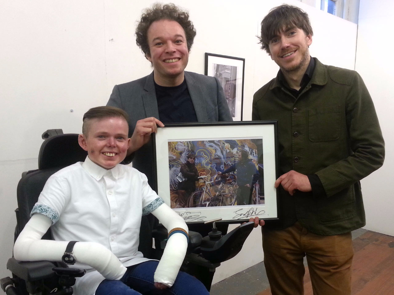 James, Jude and Simon holding up a signed print of James' photo